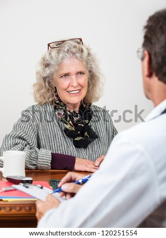 Pretty mature woman patient talks with doctor in his office. Focus on woman.