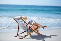 Pretty mature woman reading a book lying on deck chair on the beach