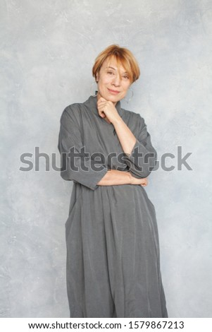 Pretty mature woman 60 years old. Perfect senior lady in gray dress