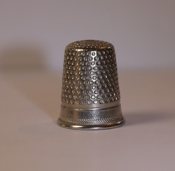 Pretty metal thimble with white background