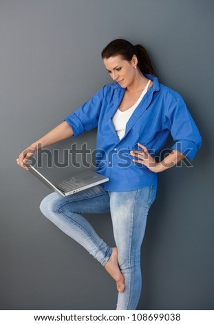 Pretty mid-adult woman standing with laptop computer, casual pose, looking at screen, smiling.