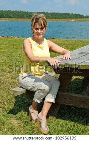 Pretty Middle Aged Woman Seating at Picnic Table on the Lake