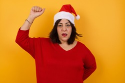 Pretty middle aged woman wearing Christmas hat,  feeling serious, strong and rebellious, raising fist up, protesting or fighting for revolution against yellow wall.