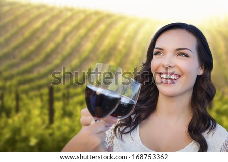 Pretty Mixed Race Young Adult Woman Enjoying A Glass of Wine in the Vineyard with Friends.