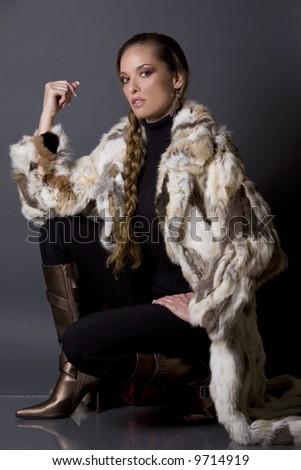 pretty model wearing fur coat and black pants indoors