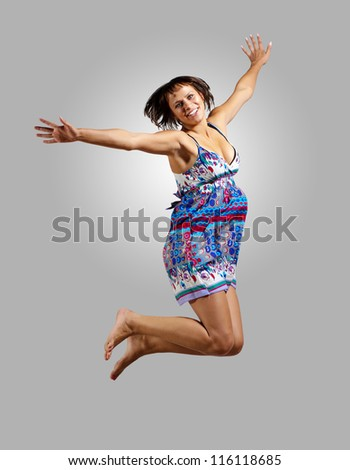 pretty modern slim hip-hop style woman jumping dancing on a colour background