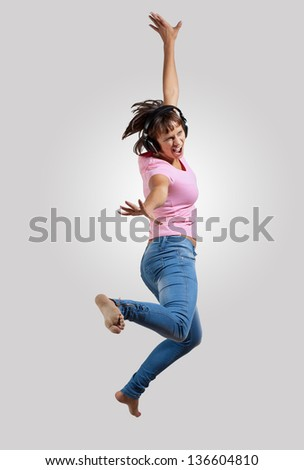 pretty modern slim hip-hop style woman jumping dancing on a grey background