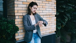Pretty modern young female millennial in casual clothes leaning against brick wall of building while checking time and impatiently waiting