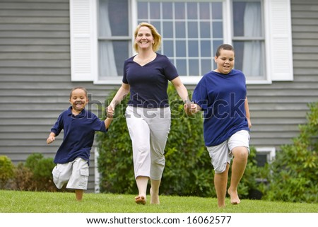 Pretty mom with her two sons running outside on grass