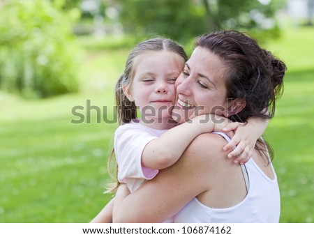 Pretty mother and daughter outside hugging portrait