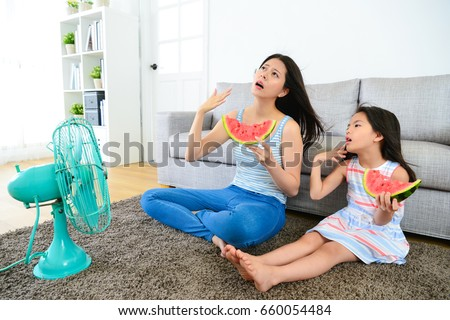 pretty mother with cute little daughter feeling very hot at summer day and eating watermelon blowing electric fan cool wind. #660054484