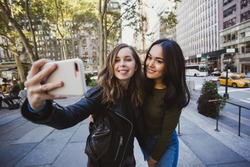 Pretty multiracial female friends taking selfie with smartphone in Manhattan, New York. Beautiful students take picture while walking in city.