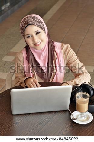 Pretty Muslim girl with laptop