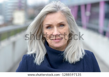 Pretty natural grey blond middle-aged woman with a lovely smile looking into the lens as she stands on an outdoor pedestrian walkway in town #1288597135