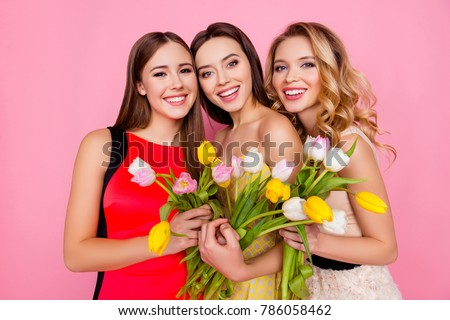 Shutterstock Pretty, nice, charming, successful trio of girls in dresses with hairstyle, having colorful tulips in hands, looking at camera, celebrating 8-march, women's day, standing over pink background