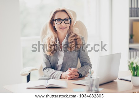 Pretty, nice, cute, perfect woman sitting at her desk on leather chair in work station, wearing glasses, formalwear, having laptop and notebook on the table, looking at camera