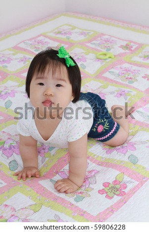 Pretty Nine Month Old Asian Baby Infant Girl Propping Self up on Bed