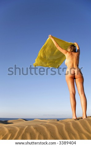 Nude In The Sand Dunes With Fabric Blowing Wind Stock