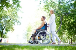 Pretty nurse walking with male patient in a wheelchair in park