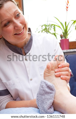 pretty Nurse washes the feet of an elderly  patient
