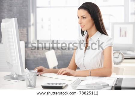 Pretty office worker girl sitting at desk in office, using desktop computer.?