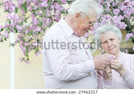 pretty old pair hold in hands small flower; outddor