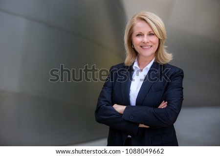 Photo of Pretty older business woman, successful confidence with arms crossed in financial building