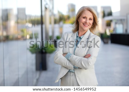Pretty older business woman, successful confidence with arms crossed near financial building #1456549952