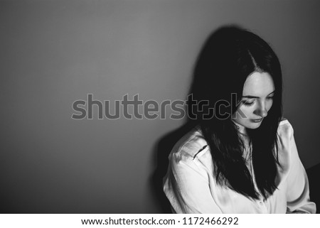Pretty pale brunette looking in the distance with her beautiful dark eyes partly closed. Atmospheric portrait of a happy dreaming girl at home alone. Wall on the background. Black and white