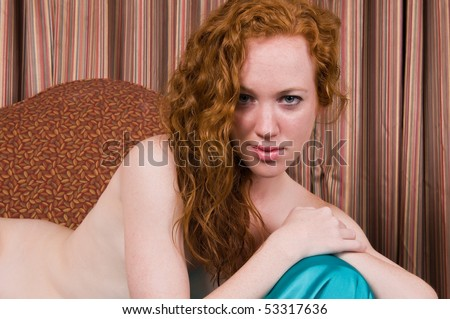 stock photo : Pretty pale redhead posing nude on an overstuffed chair