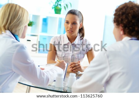 Pretty patient listening to therapeutists at medical consultation - stock photo