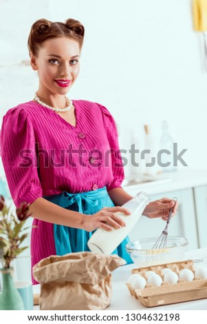 Pretty pin up girl adding milk from bottle to the ingredients for making dough and looking at camera