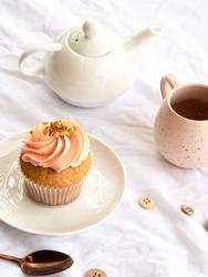 Pretty pink cupcake, pink mug and white teapot on a white pretty background