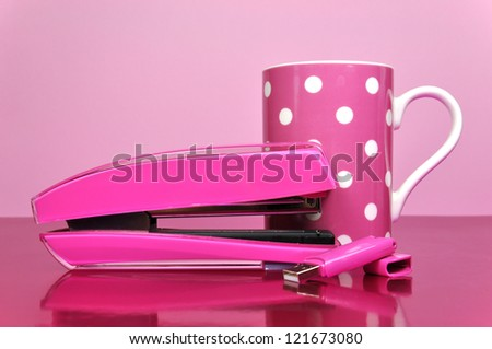 Pretty pink office accessories, stapler, pen drive, and polka dot mug, on a pink desk against a pale pink background.