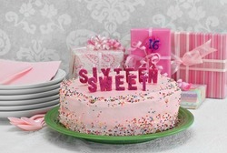 Pretty pink Sweet Sixteen birthday cake with Sweet Sixteen spelled out in candles.  Gifts behind cake.