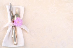 Pretty Place Setting with fork, knife, spoon, napkin, cherry blossom on cream damask tablecloth with room or space for copy, text.  Horizontal, above