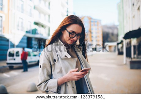Pretty positive female blogger in cool eyeglasses texting funny message for post in personal website via modern telephone connected to wireless internet.Charming tourist in good mood sending feedback