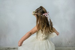 pretty preschool age girl wearing a gold sequined dress and a floral crown spinning and twirling in a pale neutral room. She is happy and having fun playing.