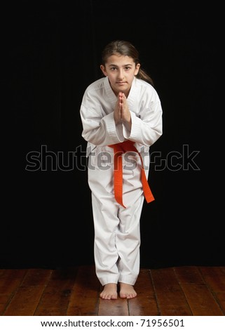 Pretty preteen girl in karate dojo bowing
