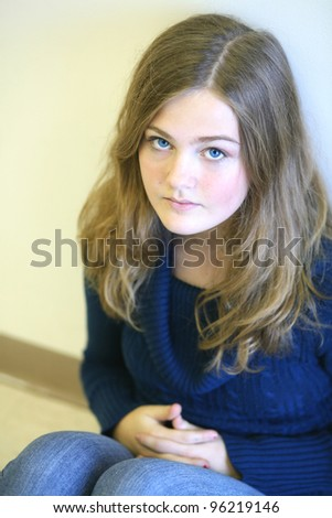 pretty preteen girl seated with big blue eyes
