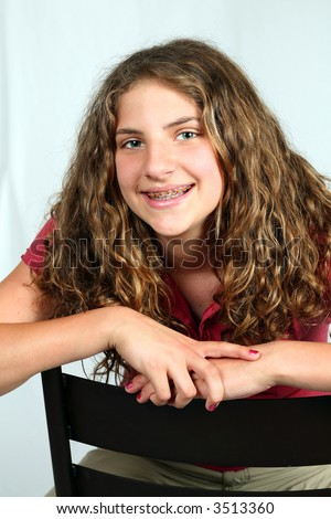 stock photo pretty preteen girl with braces seated in studio