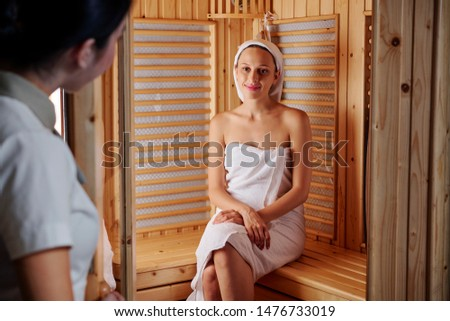 Pretty pretty Caucasian woman wrapped in towel sitting on wooden bench in sauna and enjoying steam bath
