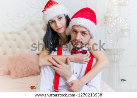 pretty pretty girl and boy with a small beard in red Christmas hats sitting on a big bed