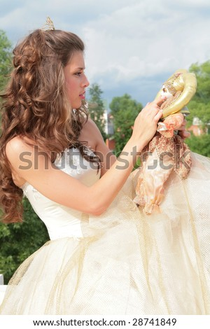 pretty princess in white-golden dress plays with loved doll