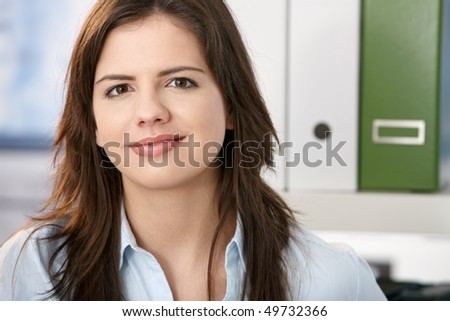 Pretty professional girl smiling at camera, face in closeup, office background. - stock photo