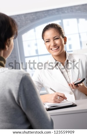 Pretty receptionist taking notes at counter, holding mobile phone, smiling at client.