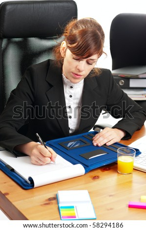 Pretty red-haired business lady or student working at a desk