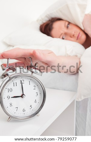 Pretty red-haired female waking up thanks to an alarm clock in the bedroom