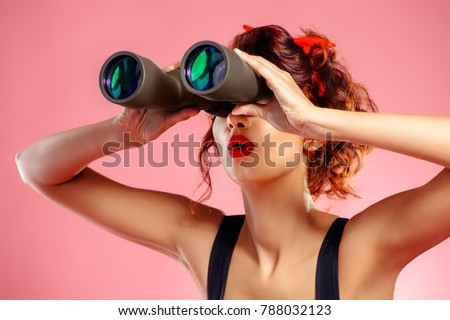 Pretty red-haired girl looks through binoculars at something over pink background. Pin-up style.  #788032123
