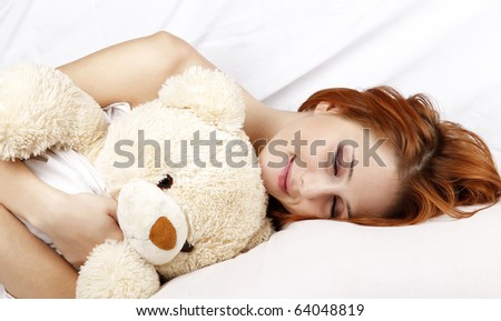 Pretty red-haired sleeping woman in white nightie lying in the bed with soft toy.